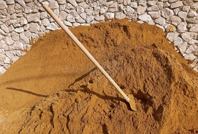 Konstruktionssand och en skyffel i sanden arkivfoton