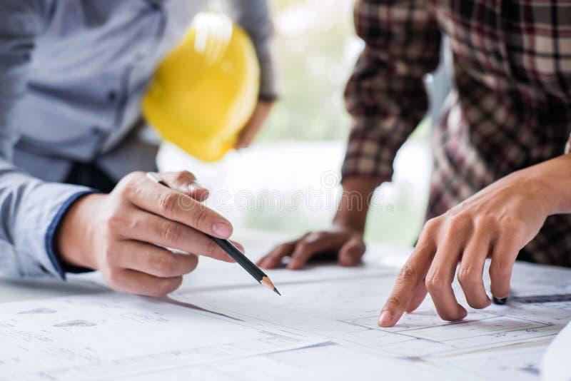 Konstruktionsteknik eller arkitekt att diskutera en ritning, medan kontrollera information på teckning och skissa mötet för fotografering för bildbyråer