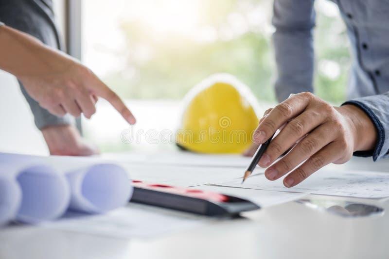 Konstruktionsteknik eller arkitekt att diskutera en ritning, medan kontrollera information på teckning och skissa mötet för arkivbilder