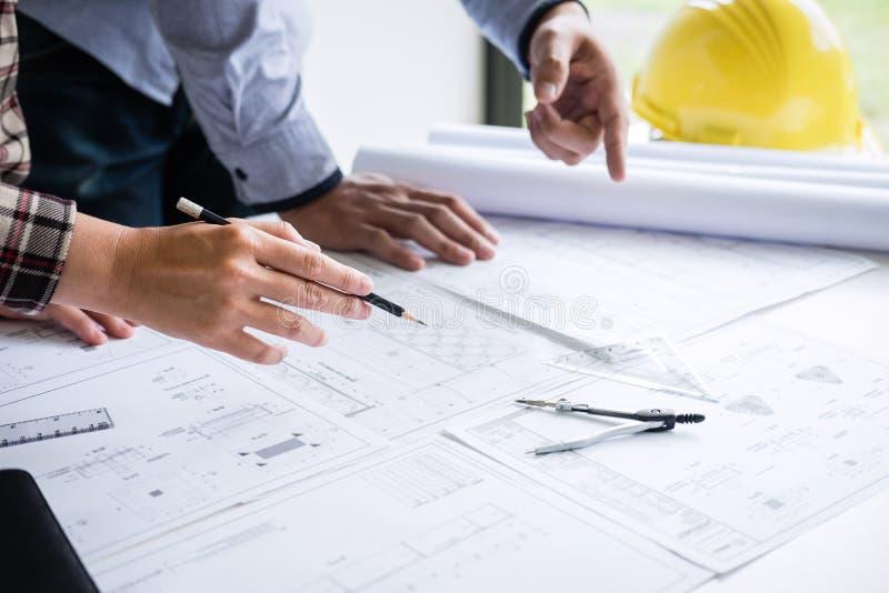 Konstruktionsteknik eller arkitekt att diskutera en ritning, medan kontrollera information på teckning och skissa mötet för royaltyfri fotografi