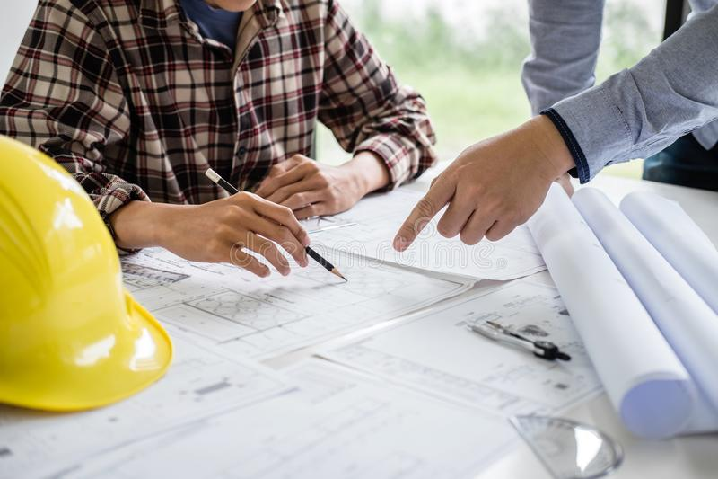 Konstruktionsteknik eller arkitekt att diskutera en ritning, medan kontrollera information på teckning och skissa mötet för royaltyfria foton