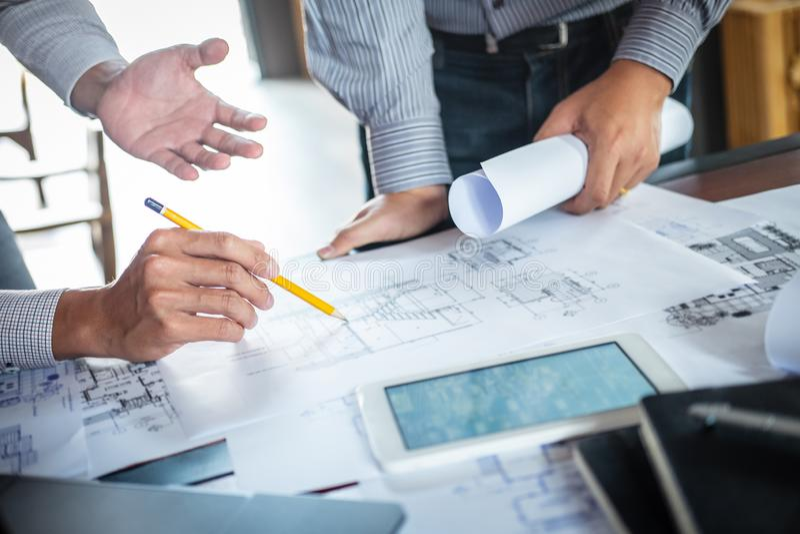 Konstruktionsteknik eller arkitekt att diskutera en ritning, medan kontrollera information p? att dra och att skissa som m?ter f? arkivfoto