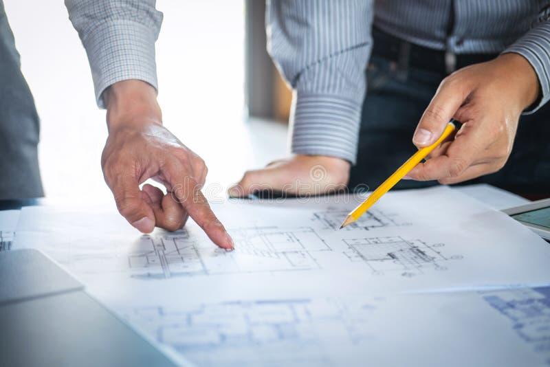 Konstruktionsteknik eller arkitekt att diskutera en ritning, medan kontrollera information p? att dra och att skissa som m?ter f? fotografering för bildbyråer