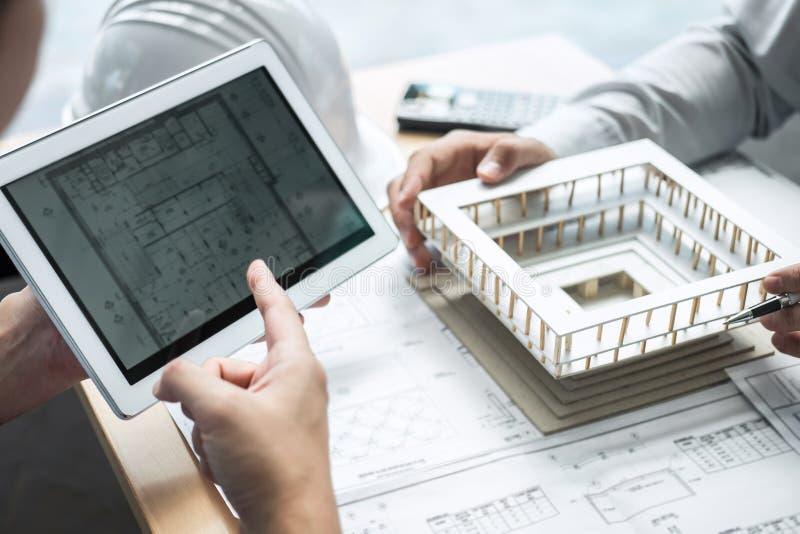 Konstruktionsteknik eller arkitekt som diskuterar en ritning och bygger modellen, medan kontrollera information på att skissa möt fotografering för bildbyråer