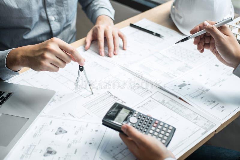 Konstruktionsteknik eller arkitekt som diskuterar en ritning och bygger modellen, medan kontrollera information på att skissa möt arkivfoton