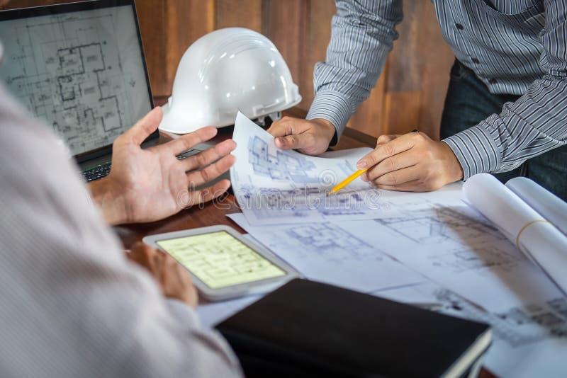 Konstruktionsteknik eller arkitekt som diskuterar en ritning och bygger modellen, medan kontrollera information p? att skissa m?t royaltyfri foto