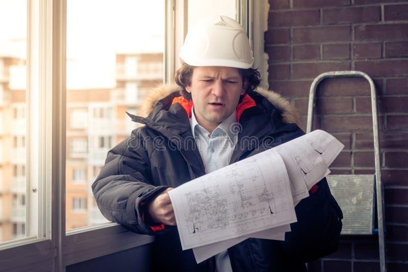 Konstruktionstekniker i hardhat med projekt i händer Mjuk fokus som tonas arkivbild