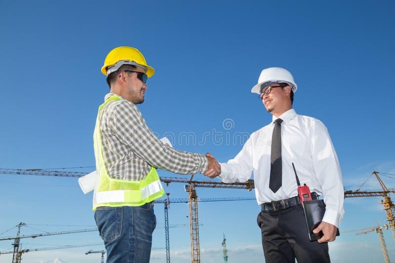 Konstruktionstekniker med arbetaren som skakar händer på konstruktion royaltyfria foton
