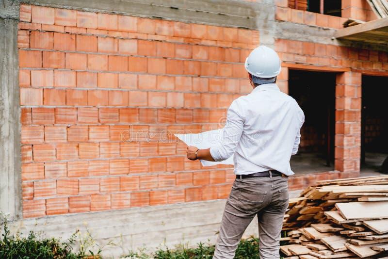Konstruktionstekniker med plan som arbetar på byggnadskonstruktionsplats tegelstenväggar, infrastruktur på konstruktionsplats royaltyfri bild