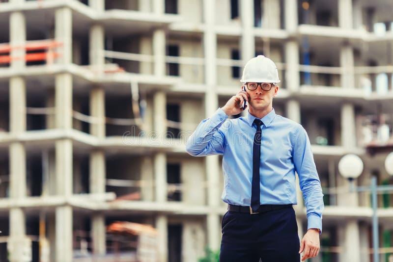 Konstruktionstekniker på konstruktionsplatsen som ser kameran och talar mobilephonen arkivfoton
