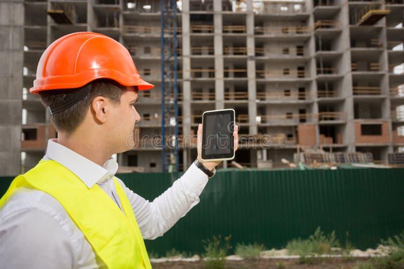 Konstruktionstekniker som kontrollerar byggnadskonstruktion med pik royaltyfri foto