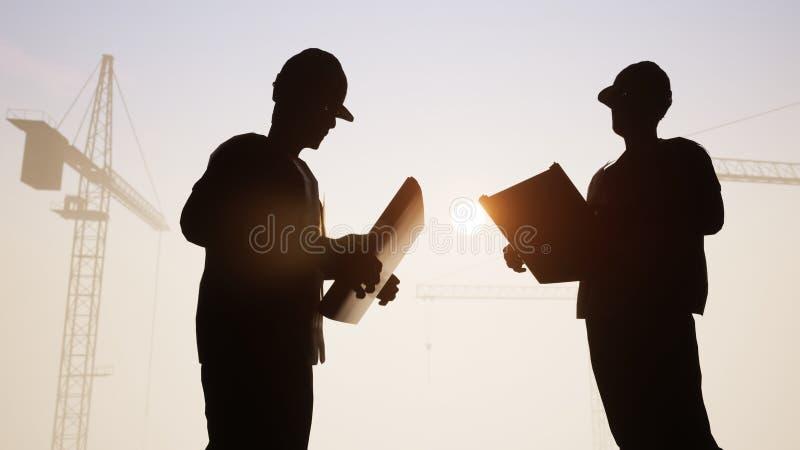 Konstruktionsteknikerer talar med kranar i baksidan stock illustrationer