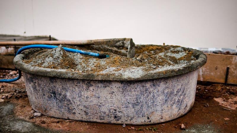 Konstruktionsutrustning som är klar för blandning av konkret cementsand, och vatten bildar den blåa slangen arkivfoto