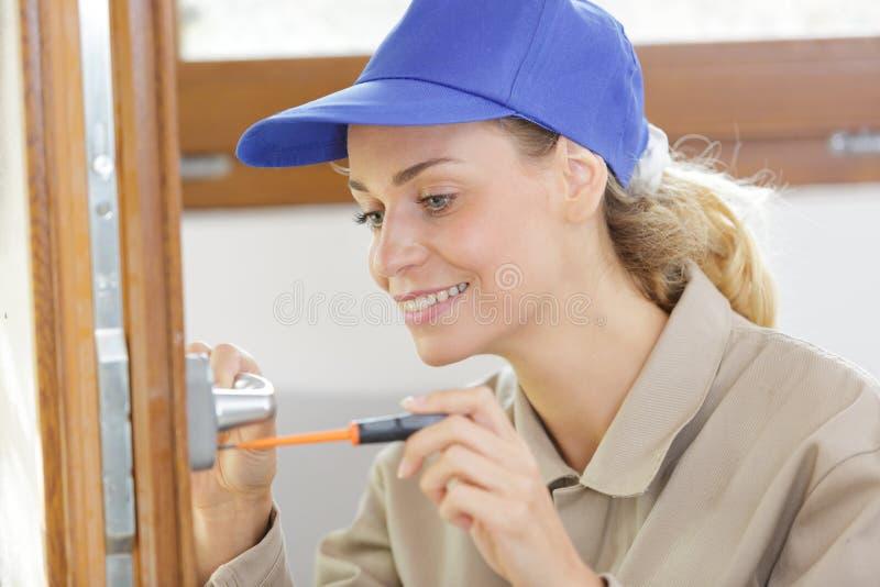 Konstruktor kobiecy pracujący przy użyciu śrubokrętu i drzwi do naprawy obrazy royalty free