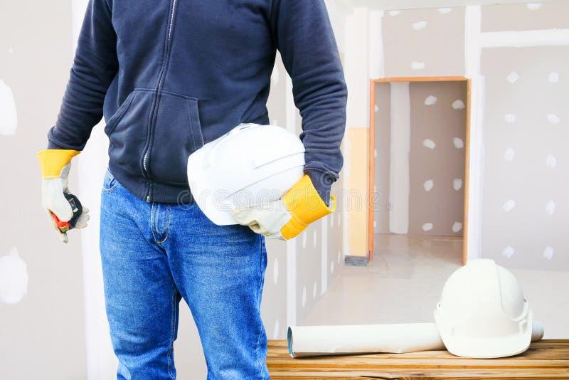 Konstruujący rękę trzyma białego zbawczego kapeluszu i papieru planu projekt na drewno stołu pracującym wewnętrznym gipsie odnawi fotografia stock