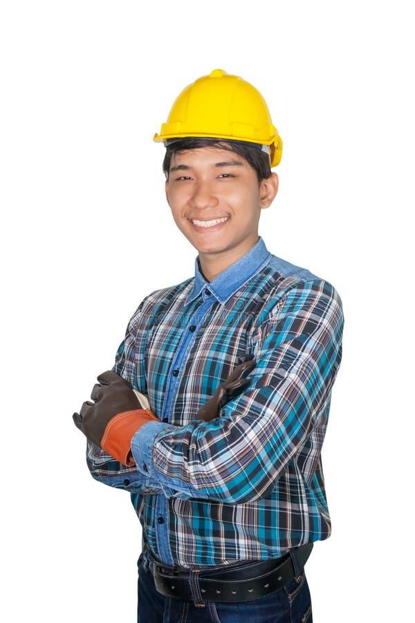 Konstruujący uśmiech budowy rękę krzyżuje na klatce piersiowej i jest ubranym Rzemienne rękawiczki z żółtym zbawczego hełma kling obrazy royalty free
