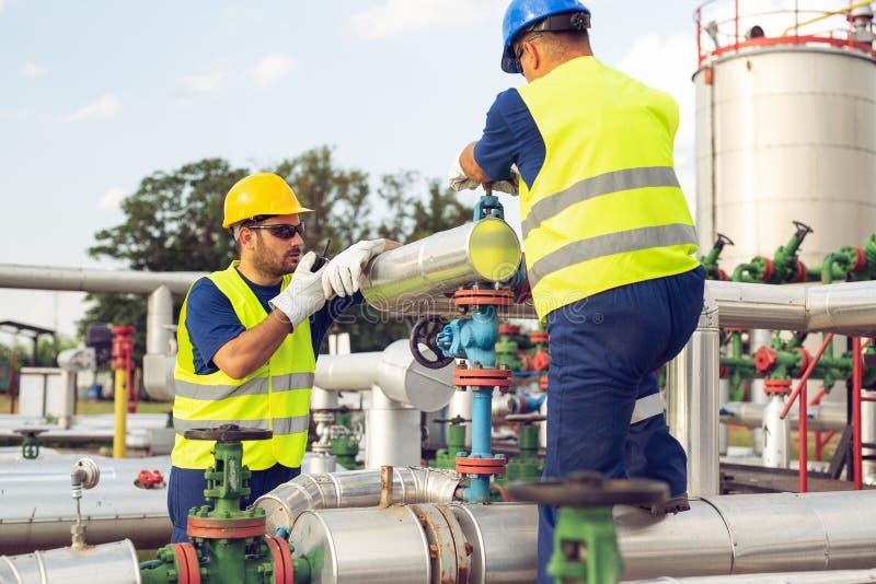 Konstruuje działanie w rafinerii ropy naftowej z opowiadać na przenośnym radiu dla kontrolować pracę obraz stock