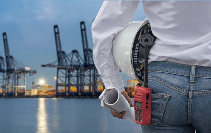 Konstruuje kobiety trzyma białego projekt z radiem dla pracownik kontrola bezpieczeństwa i hełm przy zbiornika ładunku zafrachtow fotografia stock