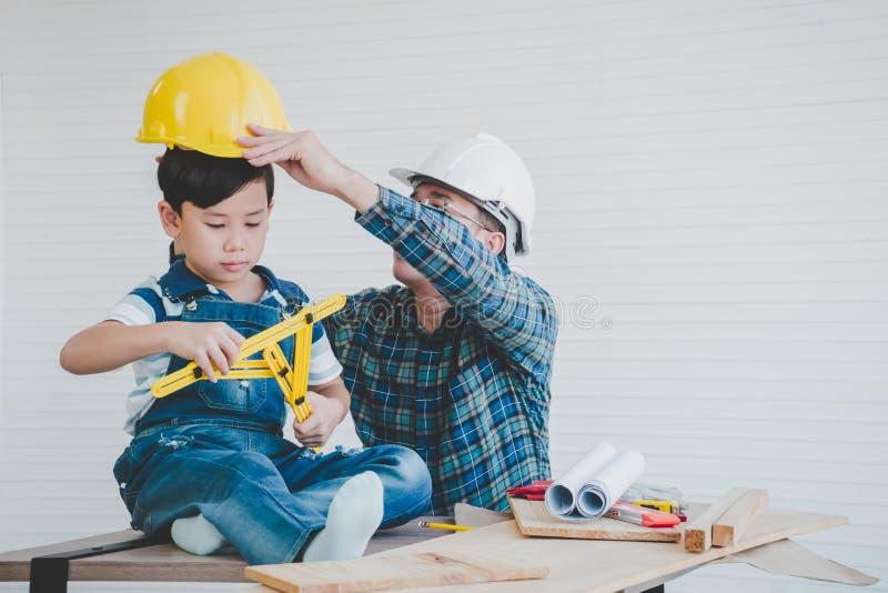 Konstruuje ojca umieszcza zbawczego kapelusz dla jego syna uczyć on o pracy bezpieczeństwie obraz stock