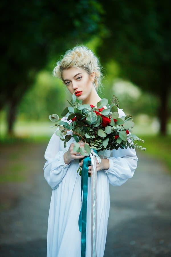 Konststående av en flicka i den vita tappningklänningen arkivfoton