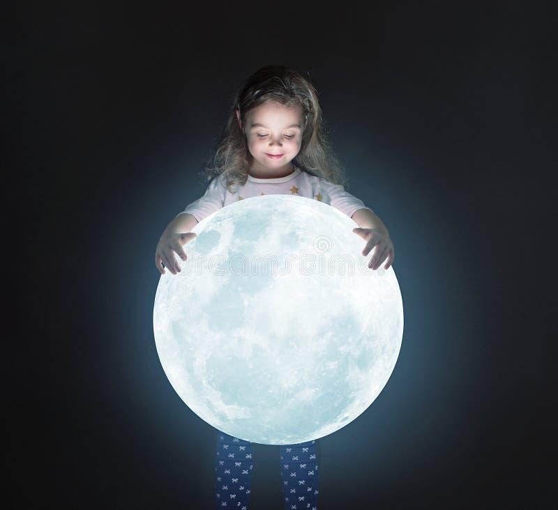 Konststående av en gullig liten flicka som rymmer en måne arkivfoto