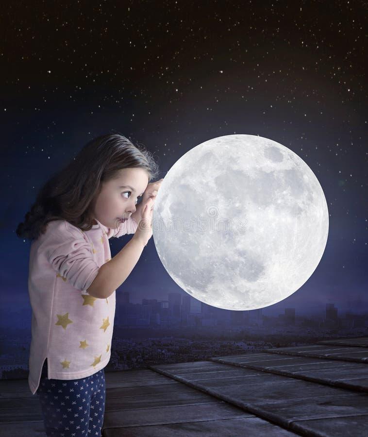 Konststående av en gullig liten flicka som rymmer en måne arkivbild