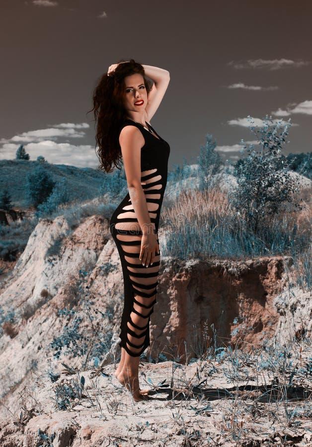 Konststående av modellen för modebrunettflicka som poserar på sandlåda Flicka på klippan arkivbild