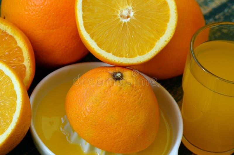 Konststilleben med juiceren för orange fruktsaft och porslinpå trätabellen royaltyfri fotografi