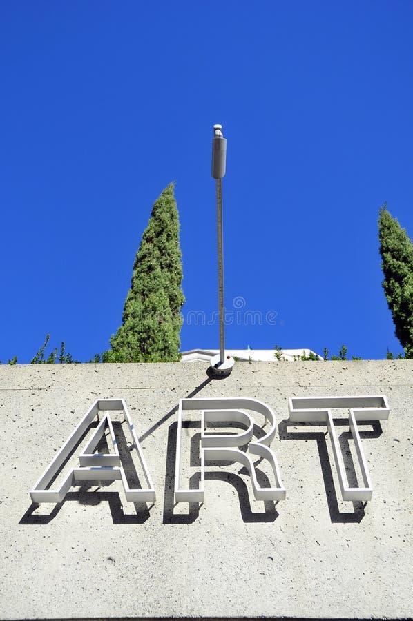 KONSTtecken på en byggnad med bakgrund för blå himmel arkivfoton