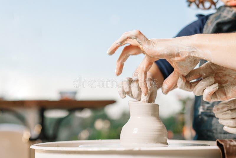 Konstterapi Kvinnors händer gör en kruka av lera på keramikers hjul Seminarium på krukmakeri royaltyfri fotografi
