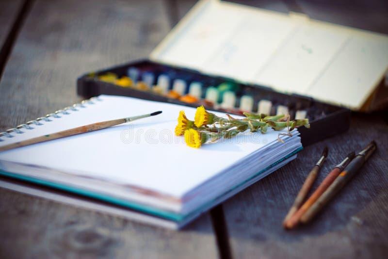 Konsttillförsel, sketchbook och bukett av blommatussilagot fotografering för bildbyråer