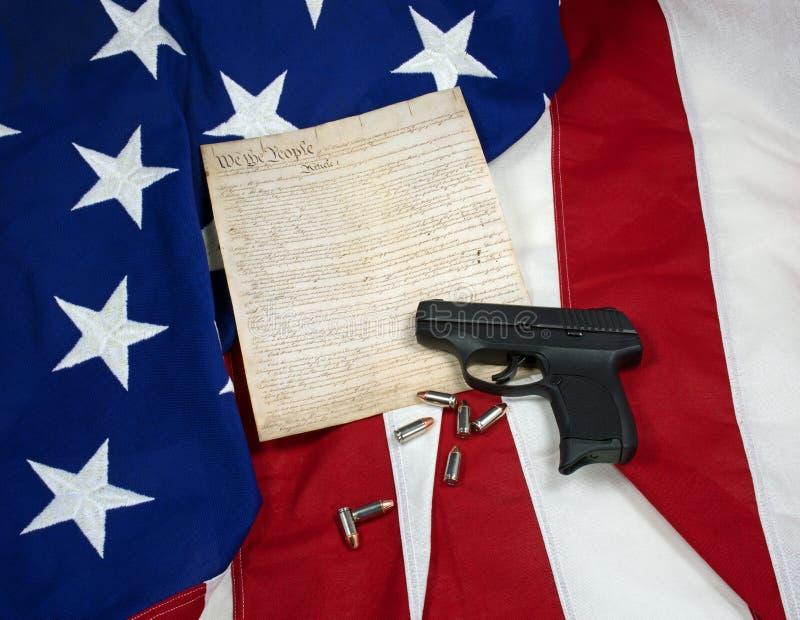 Konstytucja z ręk ładownicami na flaga amerykańskiej & pistoletem fotografia stock