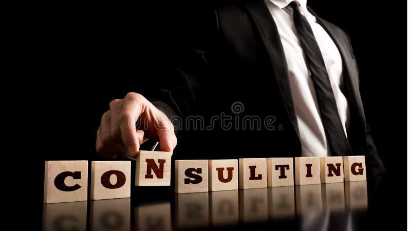 Konsulent Arranging Wooden Pieces med ConsultingText arkivfoton