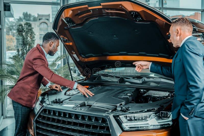 Konsulent av bilvisningslokalen som visar bilen under capote royaltyfria bilder