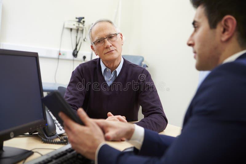 Konsulent Discussing Test Results med patienten royaltyfria foton