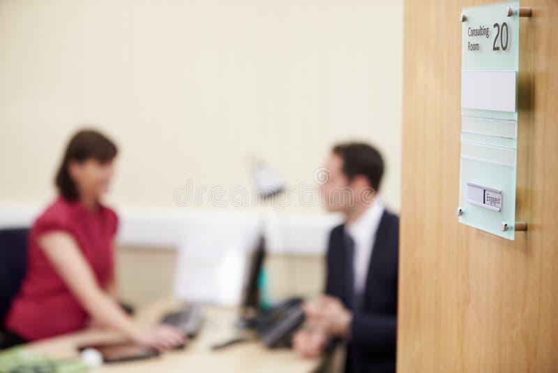 Konsulent Meeting With Patient i regeringsställning arkivbild