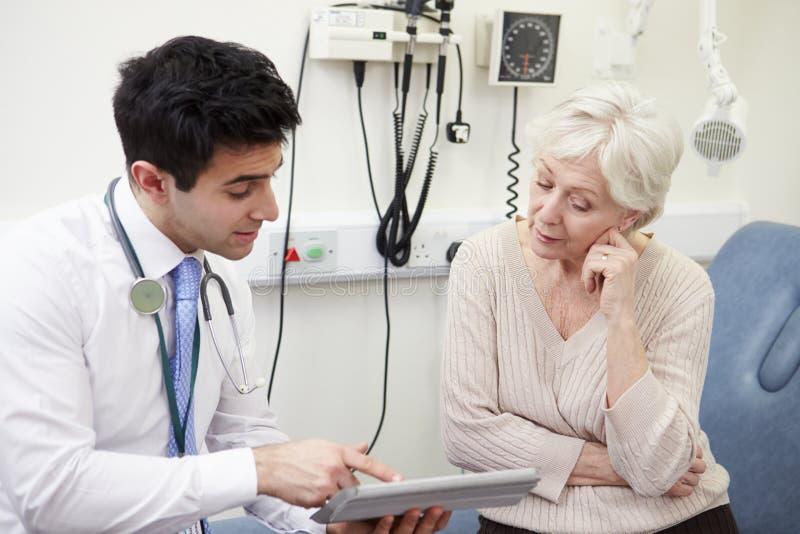 KonsulentShowing Patient Test resultat på den Digital minnestavlan arkivfoto