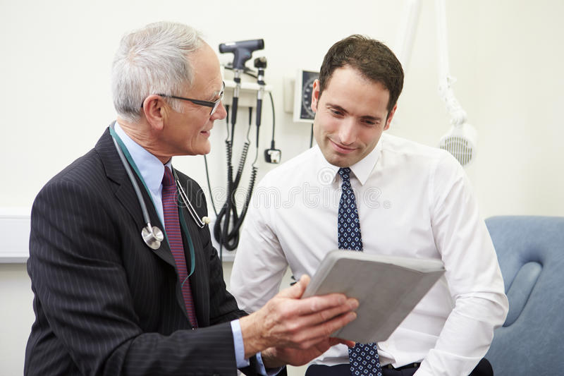 KonsulentShowing Patient Test resultat på den Digital minnestavlan arkivbild
