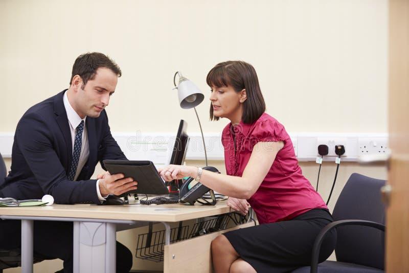 KonsulentShowing Patient Test resultat på den Digital minnestavlan royaltyfri fotografi