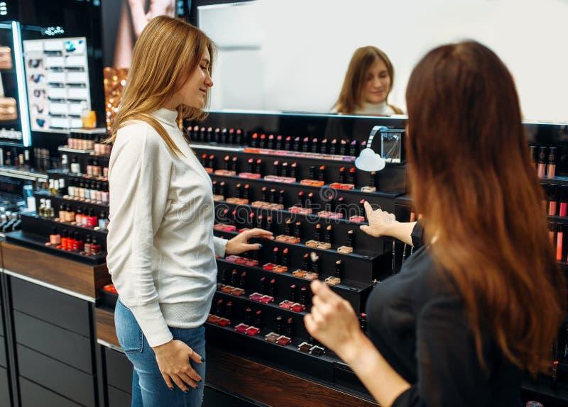 Konsultanta i kobiety klient w makijażu robi zakupy fotografia stock