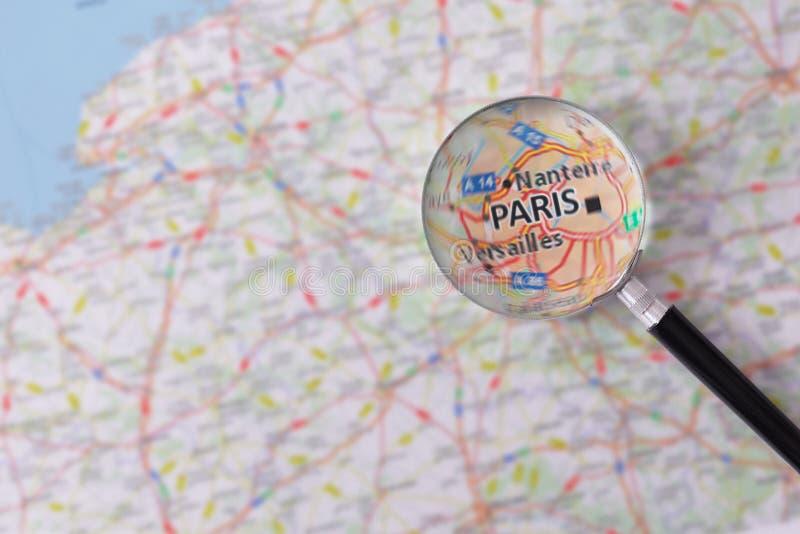 Konsultation med förstoringsglasöversikten av Paris arkivbild