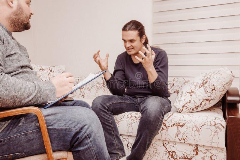Konsultera för psykolog och psykologiskt begrepp för terapiperiod Stressad man som talar om hans problem arkivbilder