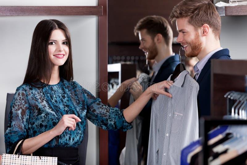 Konsultera med flickvännen, medan välja en skjorta royaltyfria foton