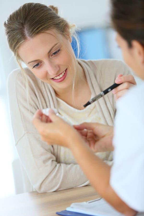 Konsulterande doktor för ung kvinna om att röka arkivbild