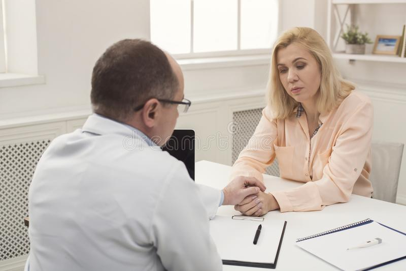 Konsulterande kvinna för allvarlig doktor i sjukhus arkivbilder