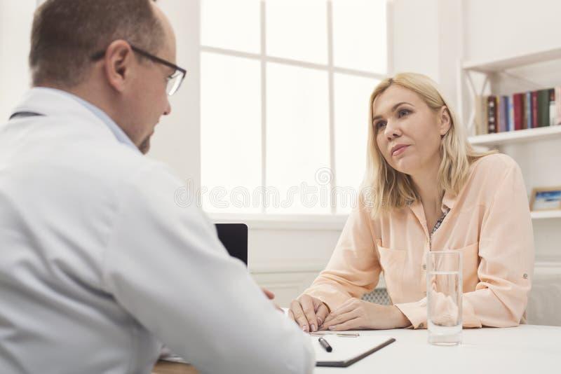 Konsulterande kvinna för allvarlig doktor i sjukhus arkivbild