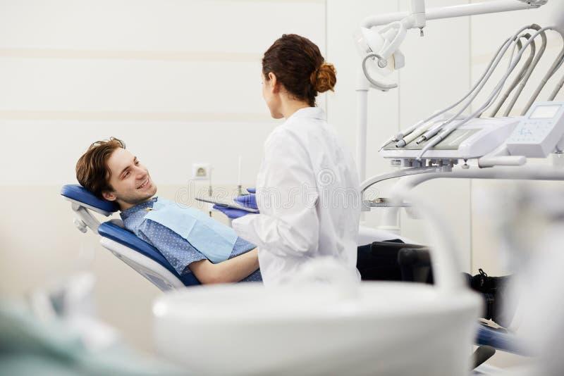 Konsulterande tandläkare för ung man royaltyfri bild