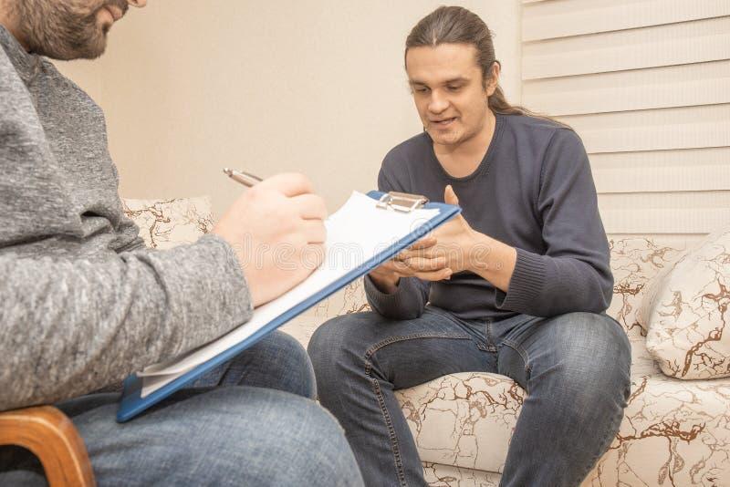 Konsulterande terapi för psykolog, mentala problem Ung man som talar om hans problem och fördjupning till psykiatern arkivfoton