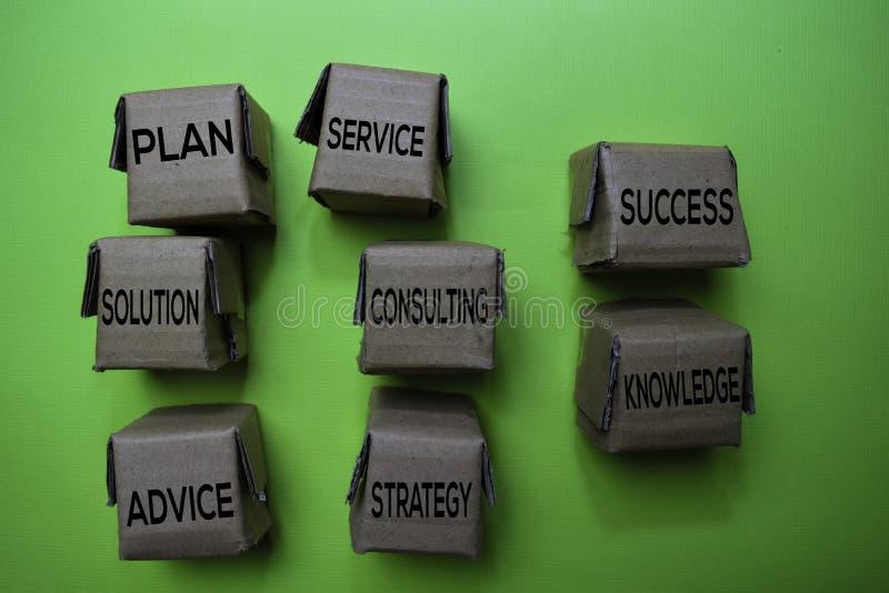 Konsultujący, rozwiązanie, plan, usługa, sukces, wiedza, strategia, rada tekst na pudełku odizolowywającym na zielonym biurku Mec obraz stock