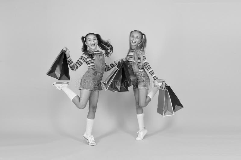 Konsumentkoncept för köpare Små flickor med shoppingväskor Försäljning och rabatter Glappade barn Små flickor med gåvor arkivfoton